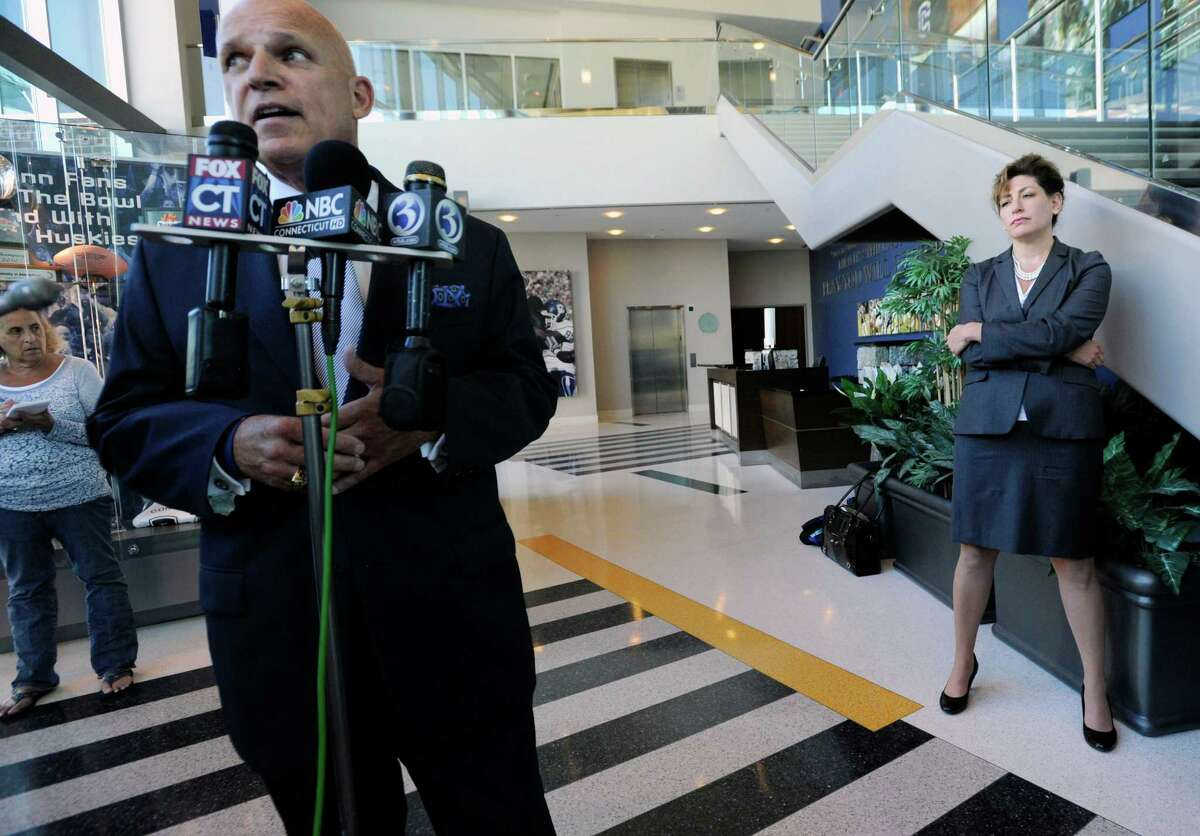 Newly-appointed Interim Director of Athletics Paul Pendergast, left, speaks to the media as university president Susan Herbst, right, looks, on during a news conference at the University of Connecticut in Storrs, Conn., Monday, Aug. 22, 2011.