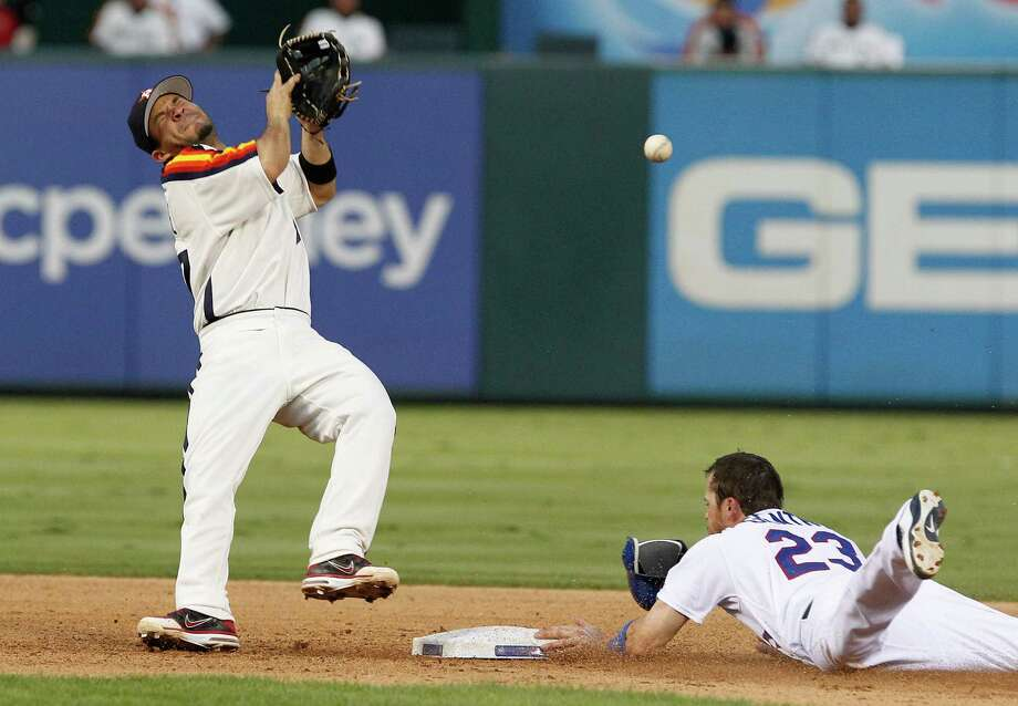 Houston Astros second baseman Jose Altuvel, left, can't handle the pick-off throw as Texas Rangers Craig Gentry (23) steals second base during the seventh inning of a baseball game Saturday, June 16, 2012, in Arlington, Texas. The Rangers won 8-3. Photo: AP