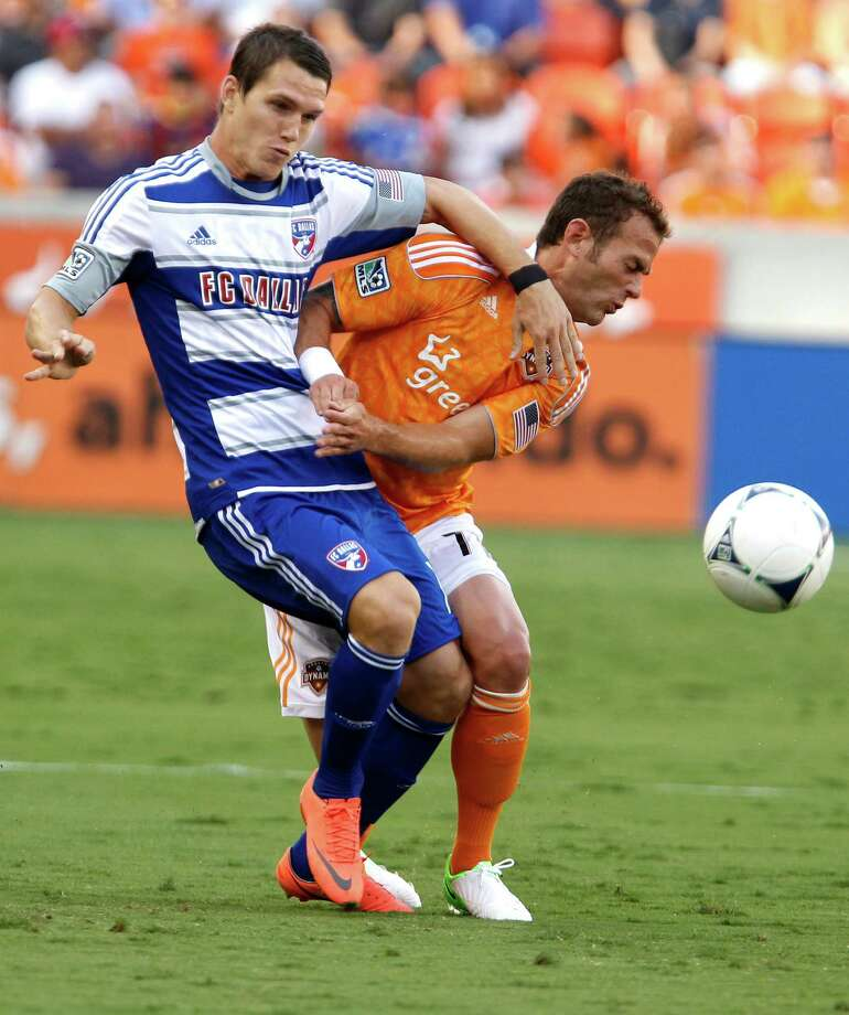 FC Dallas defender Zach Loyd left, and the Houston Dynamo midfielder Brad Davis right, collide during the first half of MLS game action at BBVA Compass Stadium Saturday, June 16, 2012, in Houston. Photo: James Nielsen, Chronicle / © Houston Chronicle 2012