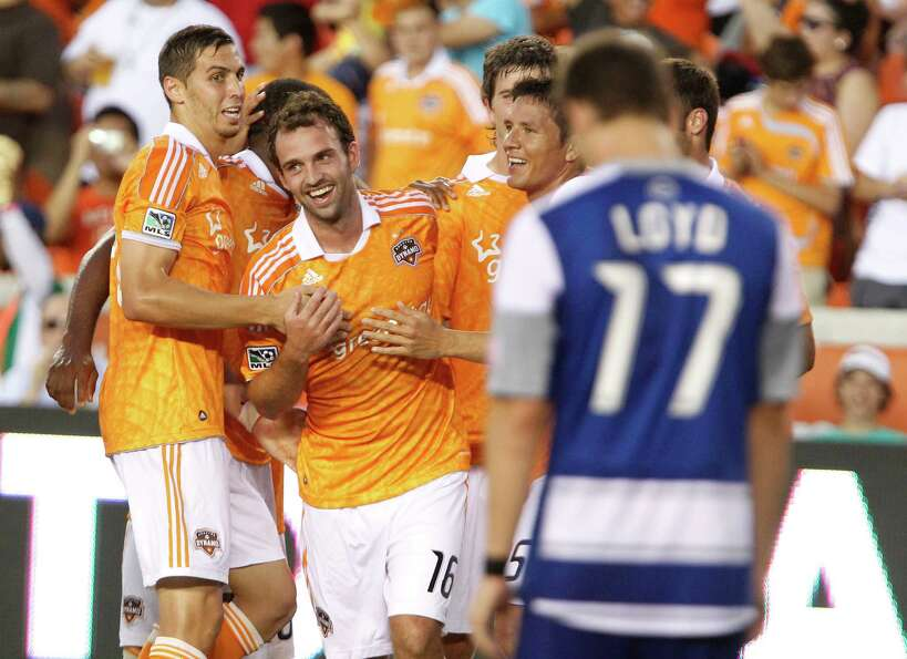 The Houston Dynamo midfielder Adam Moffat center, celebrates with teammates after scoring a goal dur