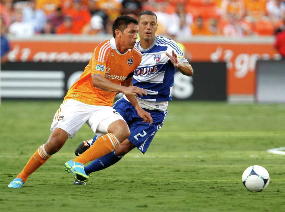The Houston Dynamo forward Brian Ching left and FC Dallas forward Fabian Castillo right chase the ball during the first half of MLS game action at BBVA Compass Stadium Saturday, June 16, 2012, in Houston. Photo: James Nielsen, Chronicle / © Houston Chronicle 2012
