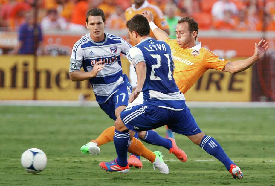 FC Dallas defender Zach Loyd left, Houston Dynamo midfielder Brad Davis center and FC Dallas midfielder Bryan Leyva right chase the ball during the first half of MLS game action at BBVA Compass Stadium Saturday, June 16, 2012, in Houston. Photo: James Nielsen, Chronicle / © Houston Chronicle 2012