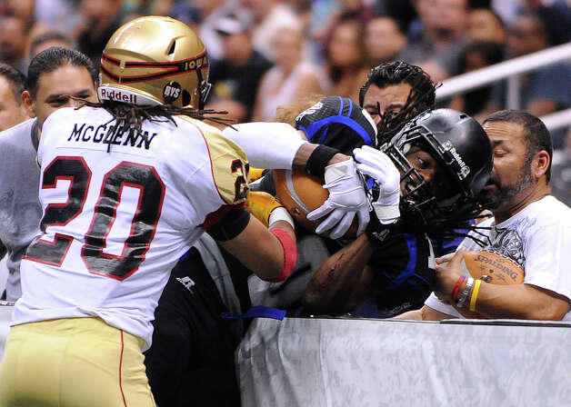 Receiver Brent Holmes of the San Antonio Talons is pushed into the retaining wall by Cameron McGlenn of the Iowa Barnstormers during arena football action at the Alamodome on Saturday, June 16, 2012. Photo: Billy Calzada, Express-News / © 2012 San Antonio Express-News