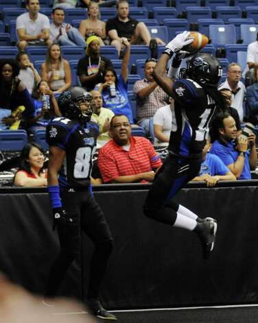 Receiver Brent Holmes, right, of the San Antonio Talons, celebrates with teammate Burl Toler after scoring a touchdown against the Iowa Barnstormers during arena football action at the Alamodome on Saturday, June 16, 2012. Photo: Billy Calzada, Express-News / © 2012 San Antonio Express-News