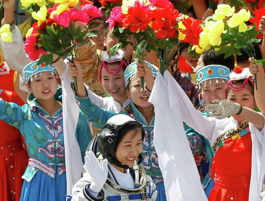 China's first female astronaut Liu Yang, bottom, waves during a sending off ceremony as she departs for the Shenzhou 9 spacecraft rocket launch pad at the Jiuquan Satellite Launch Center in Jiuquan, China, Saturday, June 16, 2012. China will send its first woman and two other astronauts into space Saturday to work on a temporary space station for about a week, in a key step toward becoming only the third nation to set up a permanent base in orbit. Photo: Ng Han Guan, Associated Press / AP