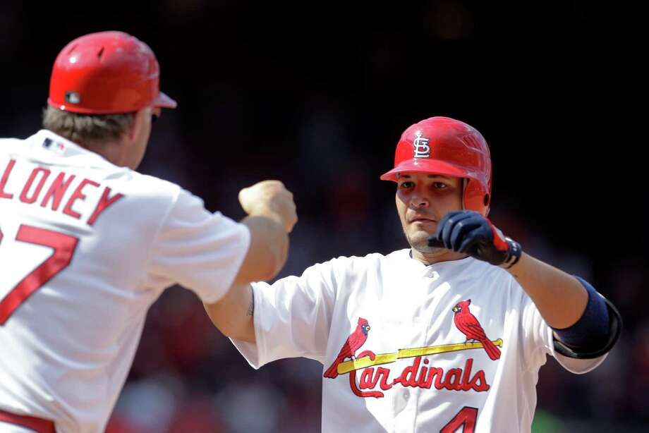 St. Louis Cardinals' Yadier Molina, right, is congratulated by first base coach Chris Maloney after hitting a two-run single during the seventh inning of a baseball game against the Kansas City Royals on Saturday, June 16, 2012, in St. Louis. The Cardinals won 10-7. (AP Photo/Jeff Roberson) Photo: Jeff Roberson
