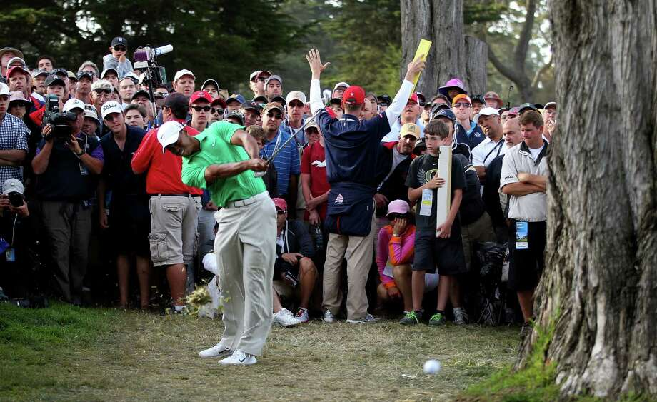 Tiger Woods hits from the rough on the 16th hole ... Photo: Jeff Gross / 2012 Getty Images