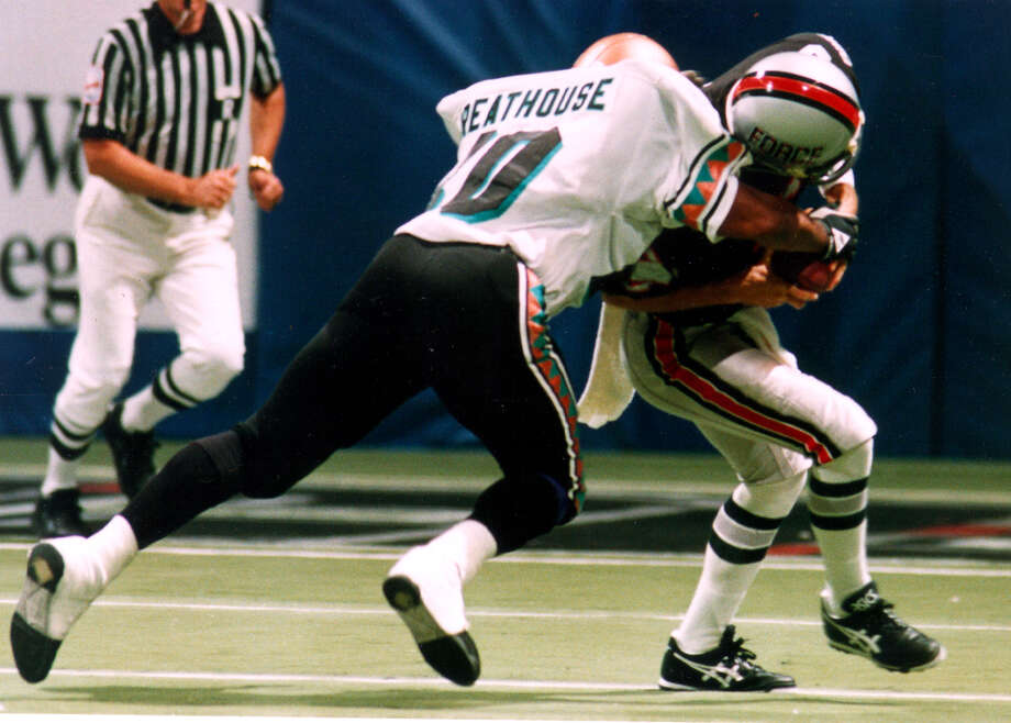 The Arizona Rattlers' Art Greathouse tackles the San Antonio Forces' Ken Lutz at Hemisfair Arena in 1992.  Bob Owen / Express-News