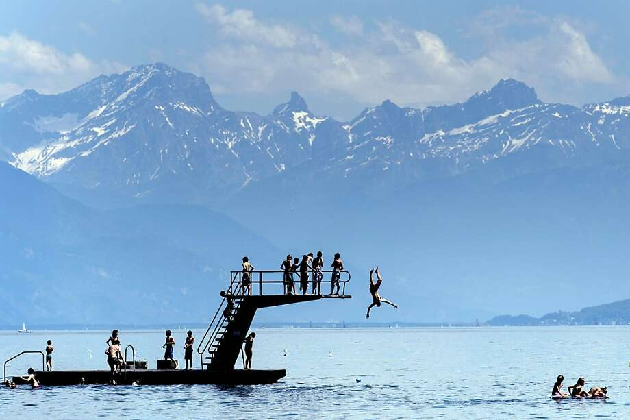 Backdropped by the Alps, youths jump into Lac Leman from a platform in Lutry, near Lausanne, Switzerland, Saturday, June 16, 2012. (AP Photo/Keystone, Laurent Gillieron) Photo: Laurent Gillieron, Associated Press