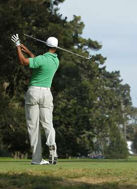 Tiger Woods lets go of his club after a not so good shot on the fourteenth hole, during the third round of the United States Open Championship being played at the Olympic Club in San Francisco, Ca., on Saturday June 16, 2012.