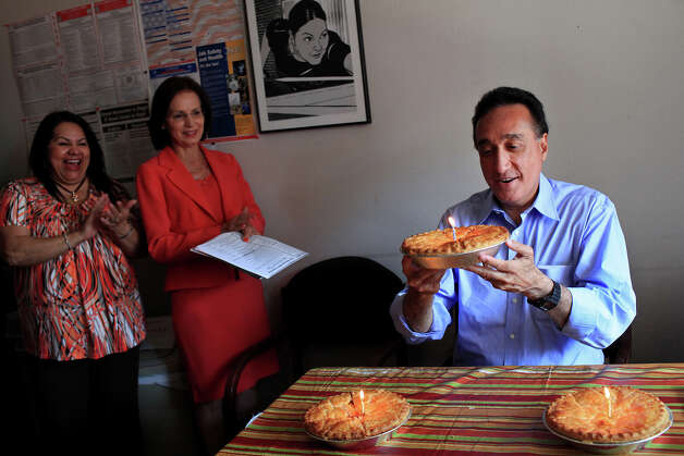 Henry Cisneros holds up his favorite kind of pie, apple, to blow out the candle while his executive assistant Sylvia Arce-Garcia, far left, and his wife, Mary Alice Cisneros, sing Happy Birthday with other building employees as he celebrates his 65th birthday at his CityView office on Monday, June 11, 2012. Photo: Lisa Krantz, San Antonio Express-News / 2012 San Antonio Express-News