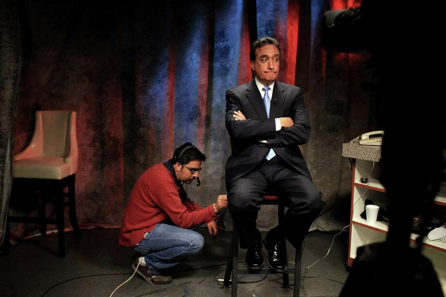 Producer/editor Erik Armenta, left, gets Henry Cisneros ready to appear on the Fox Business Network as a live guest at KABB FOX 29 in San Antonio on Wednesday, June 6, 2012. Photo: Lisa Krantz, San Antonio Express-News / 2012 San Antonio Express-News