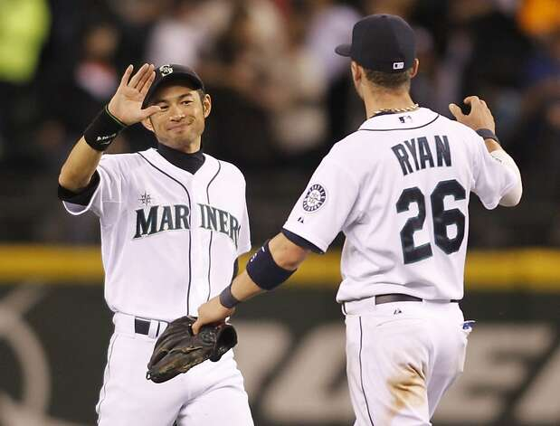 Seattle Mariners' Ichiro Suzuki, left, and Brendan Ryan celebrate the 7-4 win over the San Francisco Giants at the a baseball game in Seattle on Saturday, June 16, 2012. Suzuki is one hit away from 2500 MLB career hits. (AP Photo/John Froschauer) Photo: John Froschauer, Associated Press