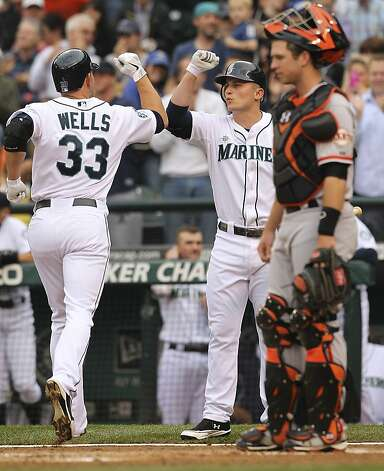 SEATTLE, WA - JUNE 16:  Casper Wells #33 of the Seattle Mariners is congratulated by Kyle Seager #15 on a solo homer against the San Francisco Giants at Safeco Field on June 16, 2012 in Seattle, Washington. (Photo by Otto Greule Jr/Getty Images) Photo: Otto Greule Jr, Getty Images