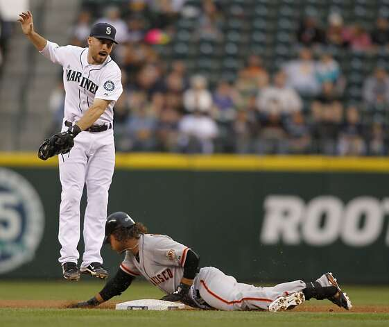 San Francisco Giants' Brandon Crawford, right, slides safely into second for a double as Seattle Mariners' Dustin Ackley comes down with a high throw during the third inning of a baseball game in Seattle on Saturday, June 16, 2012. (AP Photo/John Froschauer) Photo: John Froschauer, Associated Press