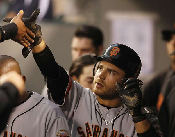 San Francisco Giants' Brandon Crawford is congratulated in the dugout after scoring on a hit by Melky Cabrera aganst the Seattle Mariners during the fourth inning of a baseball game in Seattle, Saturday, June 16, 2012. (AP Photo/John Froschauer) Photo: John Froschauer, Associated Press