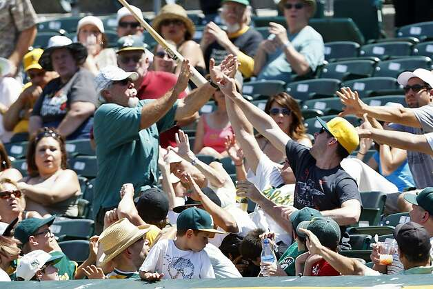 OAKLAND, CA - JUNE 16: Fans react after a bat belonging to Jemile Weeks #19 of the Oakland Athletics (not pictured) flies into the stands during the fifth inning of an interleague game against the San Diego Padres at O.co Coliseum on June 16, 2012 in Oakland, California. The Oakland Athletics defeated the San Diego Padres 6-4. (Photo by Jason O. Watson/Getty Images) Photo: Jason O. Watson, Getty Images