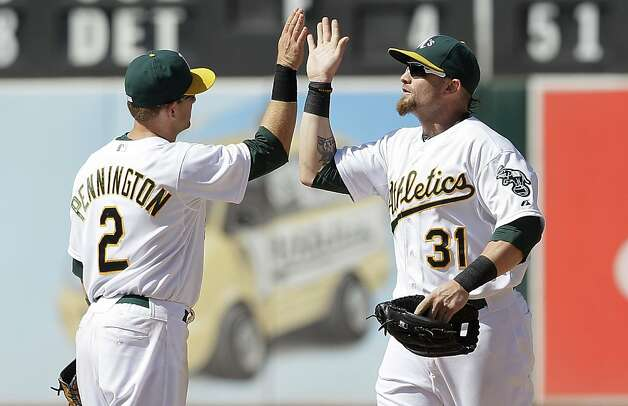Oakland Athletics' Cliff Pennington (2) and Jonny Gomes (31) celebrate after the final out of a baseball game against the San Diego Padres in Oakland, Calif., Saturday, June 16, 2012. The Athletics won 6-4. (AP Photo/Jeff Chiu) Photo: Jeff Chiu, Associated Press