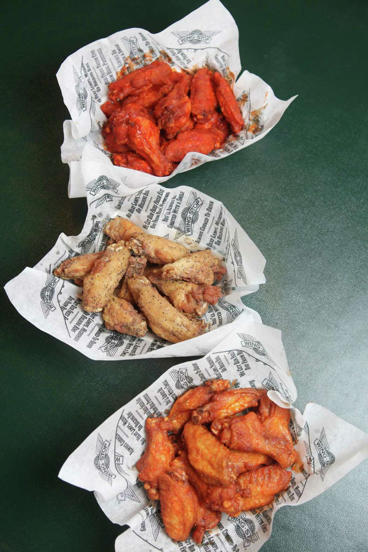 Among Wingstop's wings are (top to bottom) original hot, lemon pepper and mild, served with a variety of sauces and sides.