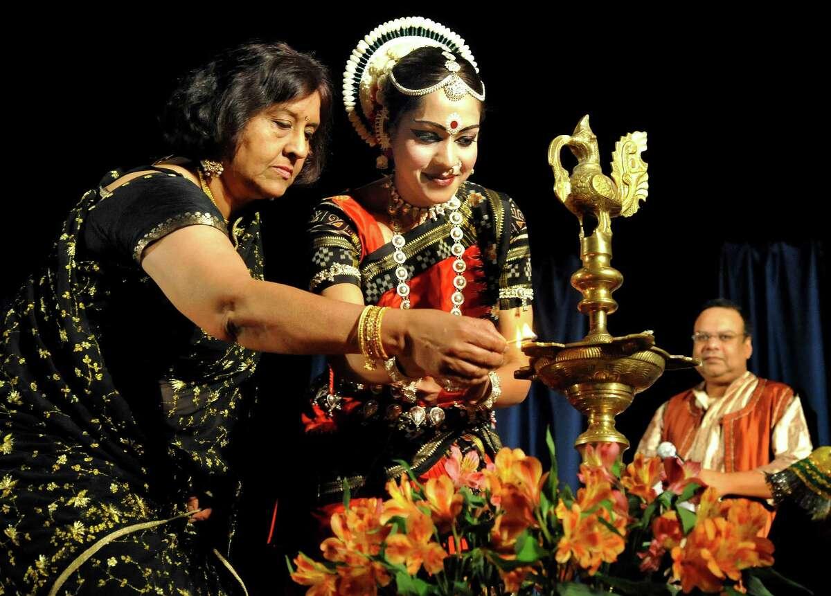 Pramila Nathan, left, and Anindita Nanda, light a candle on a part of a shrine dedicated to Natraj, lord of dance, at the start of Natyatarang 2012, in Danbury, June 16.