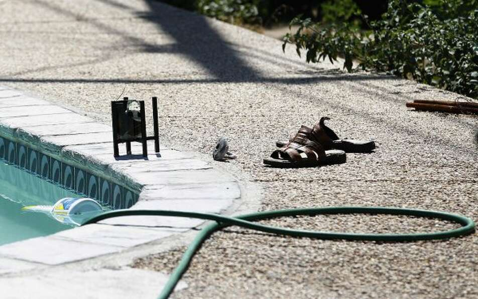 A pair of sandals lie next to a hose near the swimming pool at Rodney King's home in Rialto, Calif.,