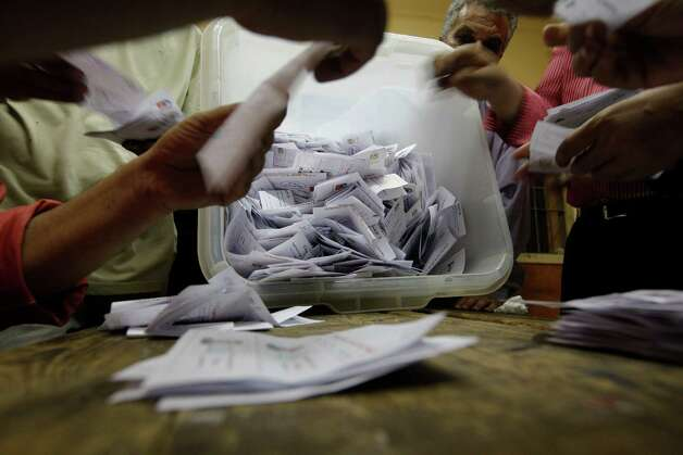 Egyptian elections officials count ballots at a polling center during the second day of the presidential runoff, in Cairo, Egypt, Sunday, June 17, 2012. Egyptians are choosing between a conservative Islamist and Hosni Mubarak's ex-prime minister in a second day of a presidential runoff that has been overshadowed by the domination of the country's military. Photo: AP
