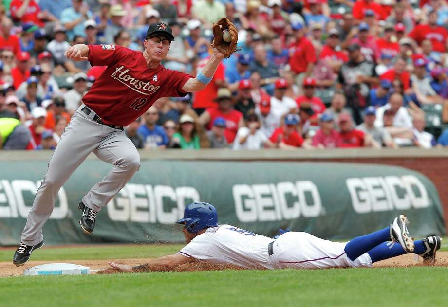 Houston Astros third baseman Brian Bixler (12) is late with the tag as Texas Rangers' Ian Kinsler slides into third base as part of a double-steal in the third inning of a baseball game, Sunday, June 17, 2012, in Arlington, Texas. Photo: AP
