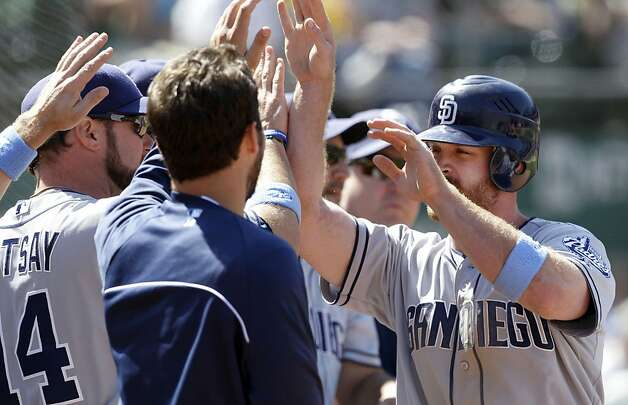 San Diego Padres' Logan Forsythe, right, celebrates with teammates after scoring on a wild pitch by Oakland Athletics pitcher Ryan Cook during the ninth inning of a baseball game in Oakland, Calif., Sunday, June 17, 2012. (AP Photo/Jeff Chiu) Photo: Jeff Chiu, Associated Press