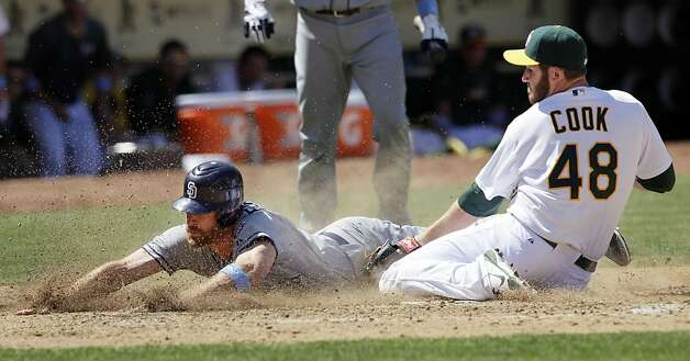 San Diego Padres' Logan Forsythe, left, scores on a wild pitch by Oakland Athletics pitcher Ryan Cook (48) during the ninth inning of a baseball game in Oakland, Calif., Sunday, June 17, 2012. (AP Photo/Jeff Chiu) Photo: Jeff Chiu, Associated Press