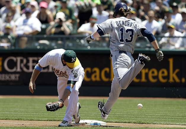 Oakland Athletics first baseman Brandon Moss, left, makes a fielding error as he fails to force out San Diego Padres' Chris Denorfia (13) at first base during the first inning of a baseball game in Oakland, Calif., Sunday, June 17, 2012. (AP Photo/Jeff Chiu) Photo: Jeff Chiu, Associated Press