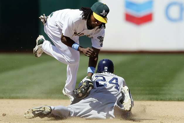 Oakland Athletics second baseman Jemile Weeks, top, leaps over San Diego Padres' Cameron Maybin (24) who was called out while stealing second base during the seventh inning of a baseball game in Oakland, Calif., Sunday, June 17, 2012. (AP Photo/Jeff Chiu) Photo: Jeff Chiu, Associated Press