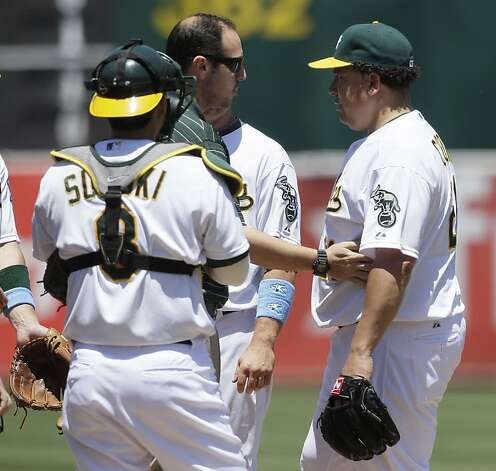 Oakland Athletics pitcher Bartolo Colon, right, is checked on by a trainer and catcher Kurt Suzuki (8) during the third inning of a baseball game against the San Diego Padres in Oakland, Calif., Sunday, June 17, 2012. Colon left the game after the play. (AP Photo/Jeff Chiu) Photo: Jeff Chiu, Associated Press