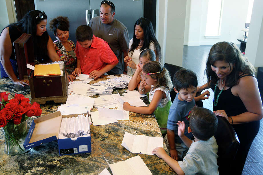 Some of the Ortiz clan gather around Jacqueline Ortiz's kitchen table as they sort through letters written by her father, Andres. Photo: Jerry Lara, San Antonio Express-News / © 2012 San Antonio Express-News