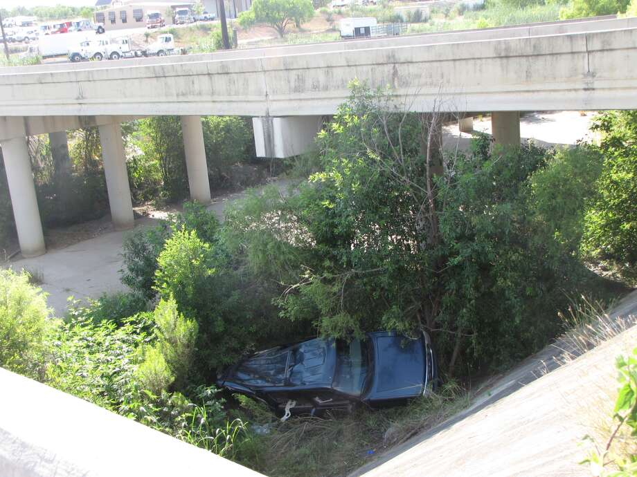 A woman was mostly uninjured Sunday afternoon, when she lost control of her Suburban before it plunged off of I-10 into a creek bed about 20 feet below, according to San Antonio police. Photo: Eva Ruth Moravec/emoravec@express-news.net