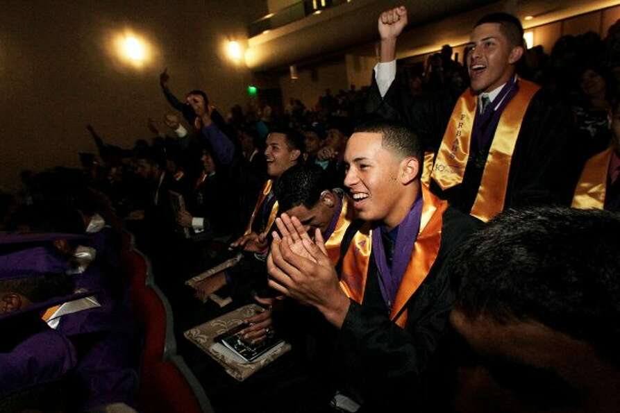 Carlos Correa laughs and claps while watching a video of senior class memories at the end of the gra