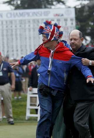 A man is removed from the awards ceremony by USGA official as he interupted the event, during the final round of the United States Open Championship being played at the Olympic Club in San Francisco, Ca., on Sunday June 17, 2012. Photo: Michael Macor, The Chronicle