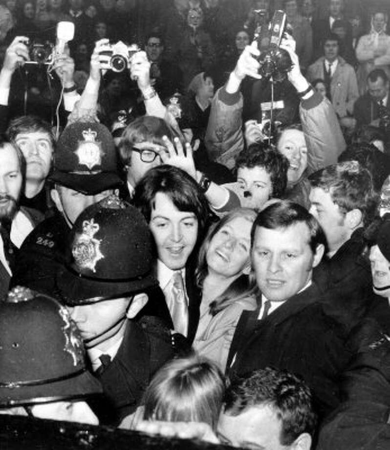 Newlyweds Paul McCartney, 26, and the American photographer formerly Linda Eastman, centre, are mobbed by a crowd of screaming fans as they are escorted by police, as the couple leave the Marylebone Town Hall Registry Office in London, after their wedding, on March 12, 1969.   (AP Photo, file) (Associated Press)
