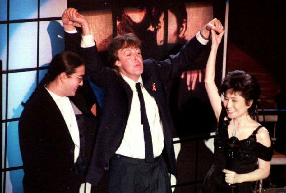 Former Beatle Paul McCartney (center) holds up the hands of the late John Lennon's son Sean Lennon (left) and his wife Yoko Ono (right) after John Lennon was inducted into the Rock and Roll Hall of Fame 19 January 1994.  (MARIA R. BASTONE/AFP/Getty Image / AFP/Getty Images)
