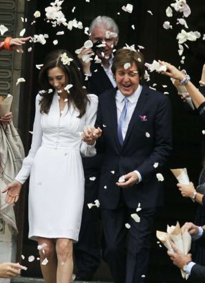 Former Beatle Paul McCartney and American heiress Nancy Shevell exit   Marylebone Town Hall in central London following their wedding Sunday Oct 9 2011.  Shevell, 51, is McCartney's third wife. They were engaged earlier this year.  (Jim Ross / Associated Press)