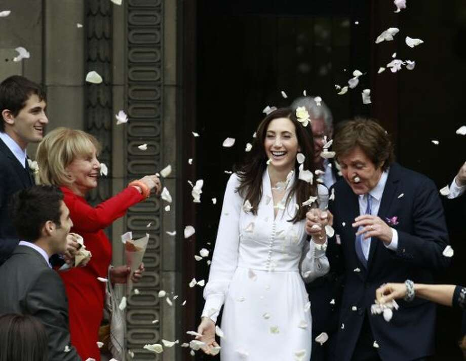 2011:  Barbara Walters throws rose petals as former Beatle Sir Paul McCartney and his wife American heiress Nancy Shevell leave Marylebone Registry Office, following their wedding in central London , Sunday Oct. 9, 2011.  Shevell, 51, is McCartney's third wife.The couple met in the Hamptons in Long Island, New York, shortly after the singer's divorce from Heather Mills in 2008 and they were engaged earlier this year. (AP Photo/Lefteris Pitarakis) (Lefteris Pitarakis / Associated Press)