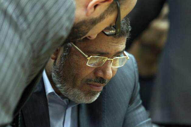 FILE - In this Sunday, June 3, 2012, file photo, Muslim Brotherhood presidential candidate Mohammed Morsi confers with an aide during a meeting with relatives, unseen, of those killed and injured during last year's revolution that forced former Egyptian president Hosni Mubarak from power, in Cairo, Egypt.  The Muslim Brotherhood has declared that its candidate, Mohammed Morsi, won Egypt's presidential election. (AP Photo/Ahmed Gomaa, File) Photo: Ahmed Gomaa