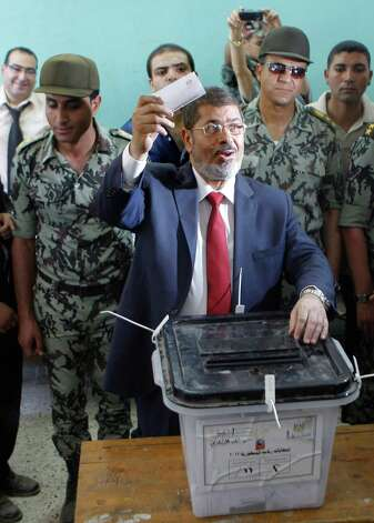 FILE - In this Saturday, June 16, 2012 file photo, Egyptian presidential candidate Mohammed Morsi waves his ballot as he prepares to cast his vote at a polling station in Zagazig, 63 miles (100 kilometers) northeast of Cairo, Egypt.  The Muslim Brotherhood has declared that its candidate, Mohammed Morsi, won Egypt's presidential election, early Monday, June 18, 2012. (AP Photo/Amr Nabil, File) Photo: Amr Nabil