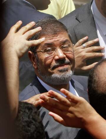 FILE - In this Saturday, June 16, 2012 file photo, supporters wave to Egyptian presidential candidate Mohammed Morsi after he cast his vote at a polling station in Zagazig, 63 miles (100 kilometers) northeast of Cairo, Egypt. (AP Photo/Amr Nabil, File) Photo: Amr Nabil