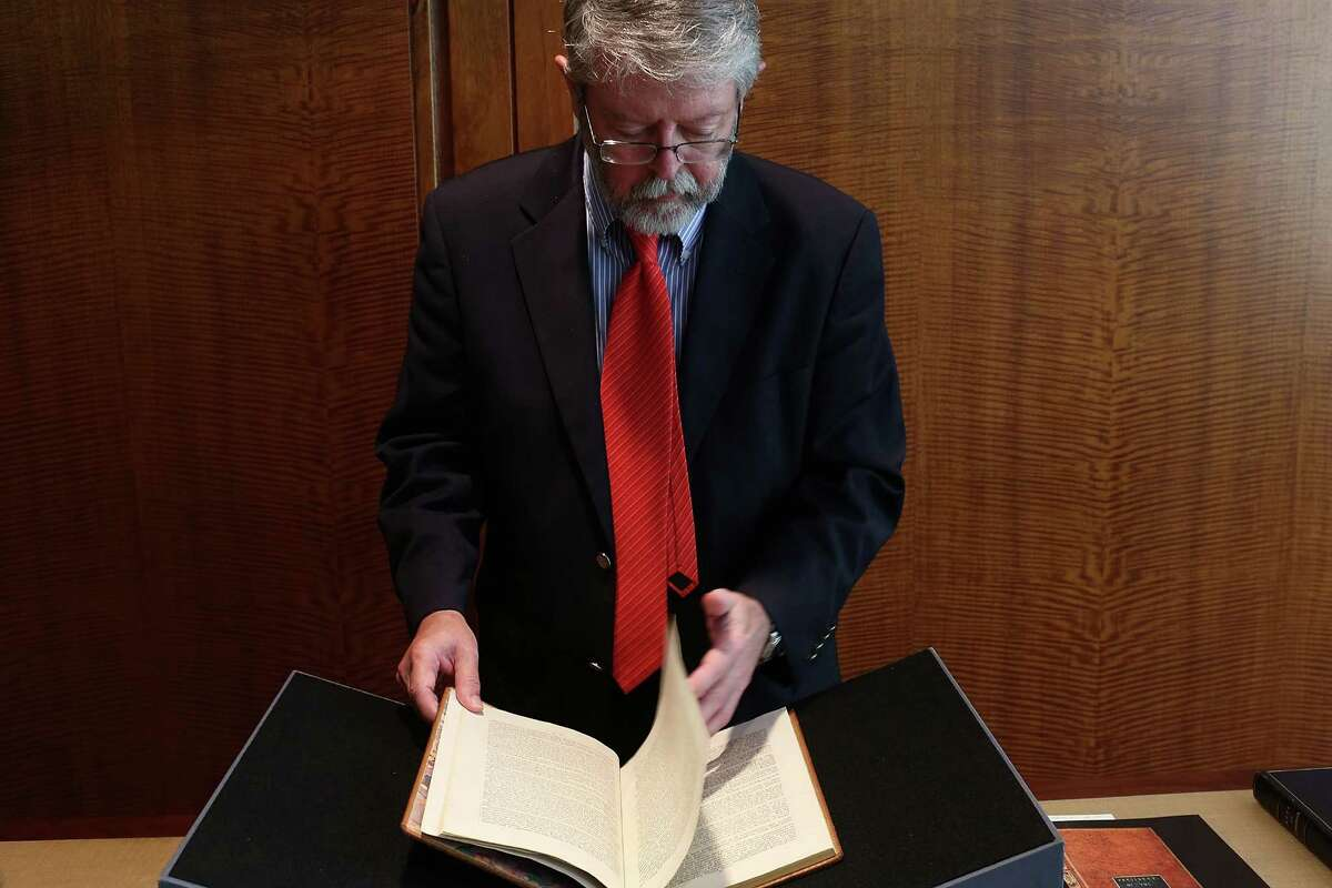 NEW YORK, NY - JUNE 15: Chris Coover, senior specialist for rare books & manuscripts at Christie's, holds a copy of former President George Washington's personal copy of the Constitution and Bill of Rights is viewed at Christie's auction house on June 15, 2012 in New York City. The artifact, which is signed and has notes by Washington, will be put up for auction on June 22 and is expected to sell for $2 million to $3 million.