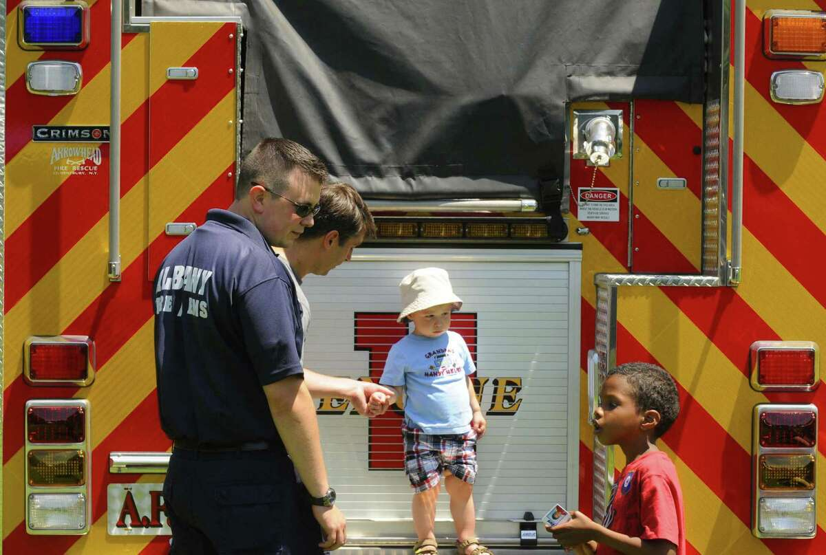 Albany firefighter Tyler Zink talks with six-year-old Jerimiah Joyner during the 8th Annual Albany Juneteenth Celebration at Washington Park in Albany N.Y. Saturday June 16, 2012. (Michael P. Farrell/Times Union)