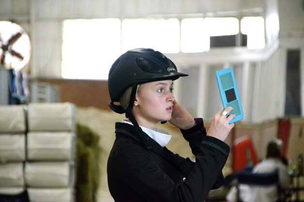 Back in the barn, 17-year-old Catherine Wachtell tucks in her hair in final preparation for her next competition at the Ox Ridge Charity Horse Show.  Thursday, June 14, 2012, Darien, Conn. Photo: Jeanna Petersen Shepard
