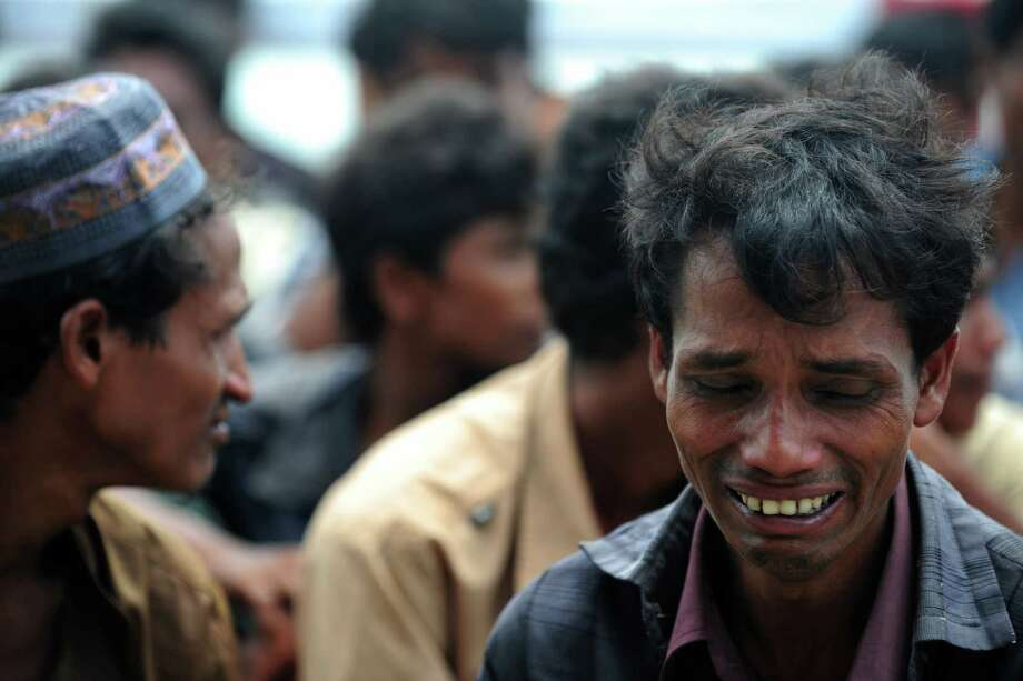 A Rohingya Muslim from Myanmar, who tried to cross the Naf river into Bangladesh to escape sectarian violence, reacts while kept under watch by Bangladeshi security officials after disembarking from an intercepted boat in Teknaf on June 18, 2012. At least 50 people have died in western Myanmar's Rakhine state in more than a week of sectarian violence and revenge attacks between Buddhists and Muslim Rohingya. Bangladesh is coming under increasing international pressure to open its border to Rohingya, but has so far refused to do so. AFP PHOTO/ Munir uz ZAMANMUNIR UZ ZAMAN/AFP/GettyImages Photo: MUNIR UZ ZAMAN, AFP/Getty Images / AFP