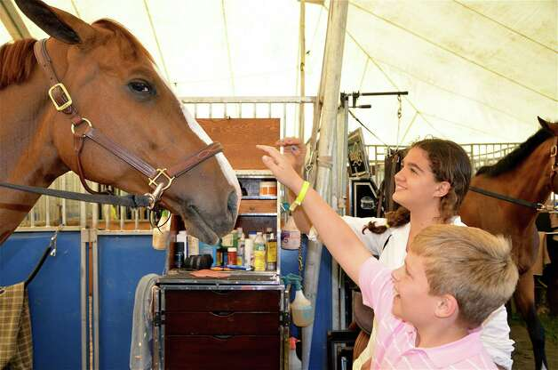 Graydon Roedel and Rachel Hyatt try to cheer up a horse in one of the barns at the Ox Ridge Hunt Club last Saturday, June 16, 2012 in Darien, Conn. Photo: Jeanna Petersen Shepard