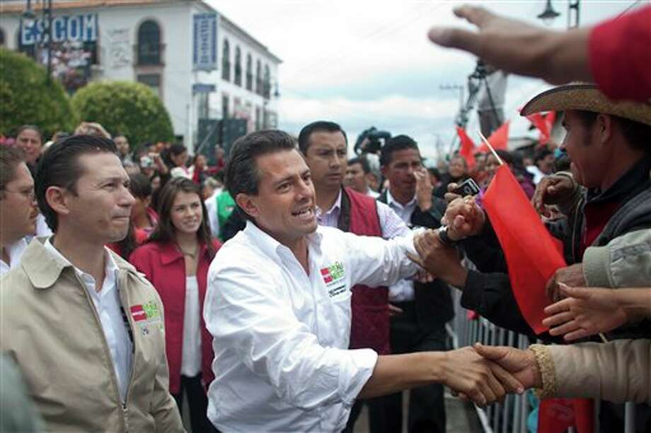 Presidential candidate Enrique Pena Nieto, of the Institutional Revolutionary Party, center, greets supporters during a campaign rally in Atlacomulco, Mexico, Sunday, June 17, 2012. Mexico will hold presidential elections on July 1. (AP Photo/Alexandre Meneghini) (AP)