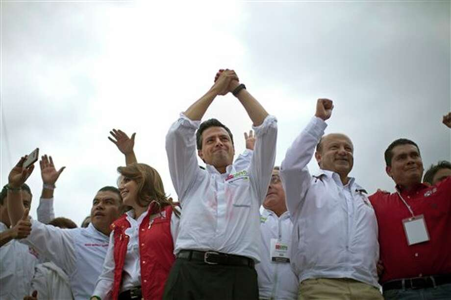 Presidential candidate Enrique Pena Nieto, of the Institutional Revolutionary Party, center, gestures to supporters during a campaign rally in Atlacomulco, Mexico, Sunday, June 17, 2012. Mexico will hold presidential elections on July 1. (AP Photo/Alexandre Meneghini) (AP)